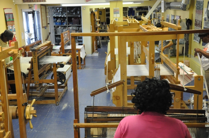 Weavehouse workers making products on donated looms using recycled materials.