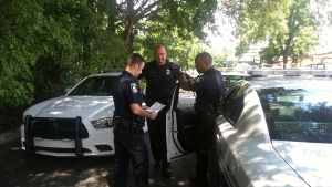 Decatur Police Officers compare notes in the parking lot of Decatur High School.
