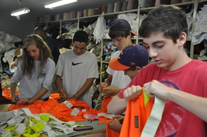 Students from The Lovett School helping to break down vests provided to re:loom by Delta.