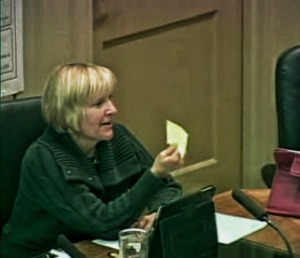 During the Nov. 4 Decatur, Ga. City Commission meeting, Commissioner Patti Garrett holds up one of the cards left on homes in Decatur by Atlantahousebuyer.com