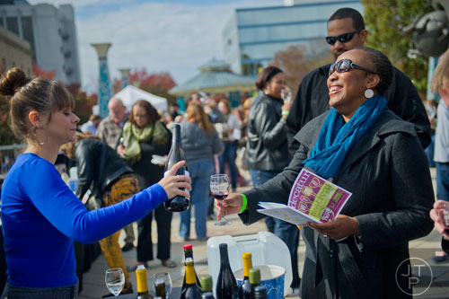 Margo Kemmerer (left) pours a glass of wine for Shauntice Allen during the Decatur Wine Festival on Saturday, November 9, 2013. Photo by: Jonathan Phillips